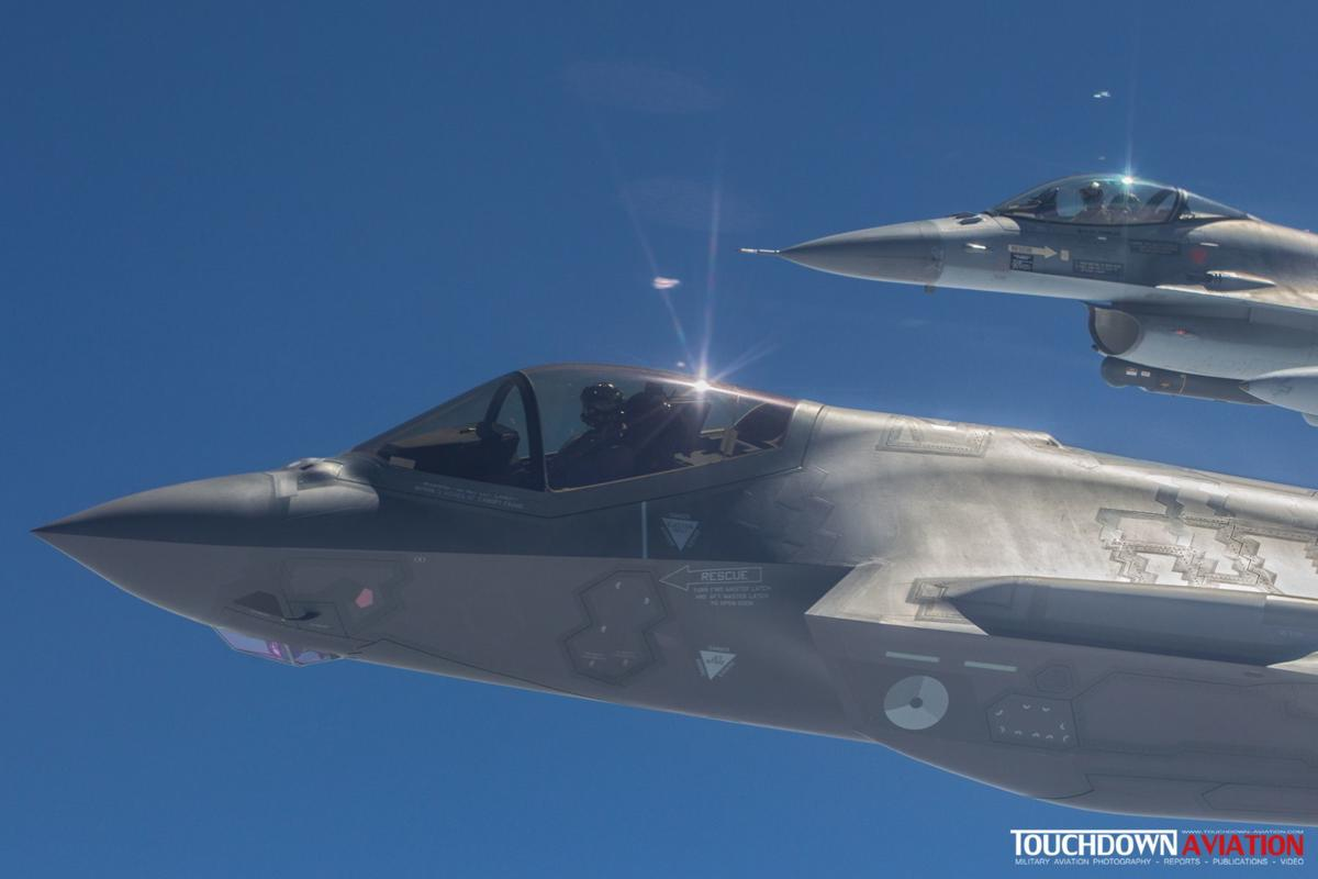 A close up of the F-35A flying alongside the KDC-10 tanker with a F-16 in the background